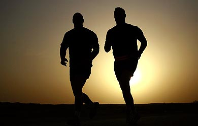 Sunset silhouette of two men running